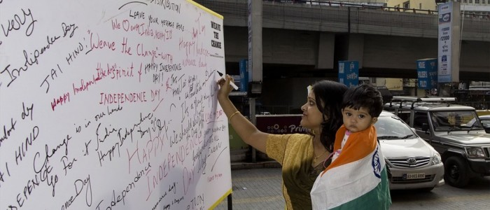 A woman voting by signature with her kid holding national flag